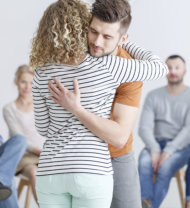man hugging the counselor with a group of audience watching behind them