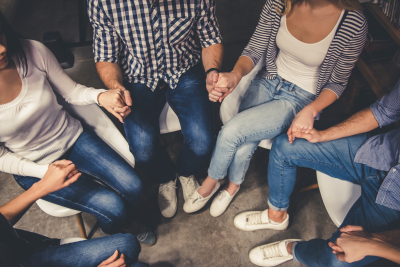 Young people are sitting in circle and holding hands while having a meeting in the modern library
