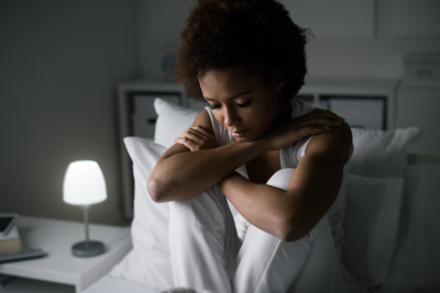 depressed woman sitting on her bed late at night